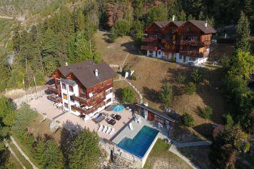 Luftaufnahme auf die Ferienwohnungen von Ferienwallis mit Pool und Sitzplatz
